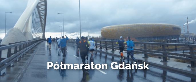 Zdjęcie z półmaratonu w Gdańsku, ludzie biegnący przez most w tle areny
